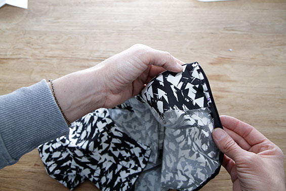 13) Fold the facing inside, fold under in the centre back and secure by hand. Repeat at the shoulder seams.